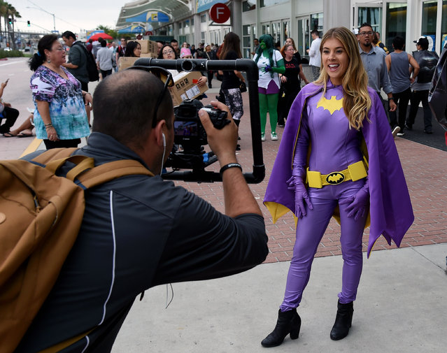 """FOX Sports San Diego's Ally Sturm, dressed in Batman attire, films for the network's """"Padres POV"""" show outside the San Diego Convention Center during preview night of Comic-Con International 2015 on July 8, 2015 in San Diego, California. (Photo by Ethan Miller/Getty Images)"""