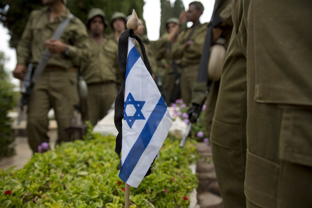 Israeli soldiers stand next to a small flag with a black ribbon placed on a grave of a fallen soldier on the eve of memorial Day in Kiryat Shaul military cemetery in Tel Aviv, Israel, Tuesday, May 10, 2016. (Photo by Ariel Schalit/AP Photo)