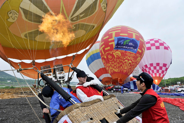 Participants fire their hot air balloon with an opera mask design on it during a hot air balloon competition in Hefei, Anhui province, China April 27, 2016. (Photo by Reuters/Stringer)