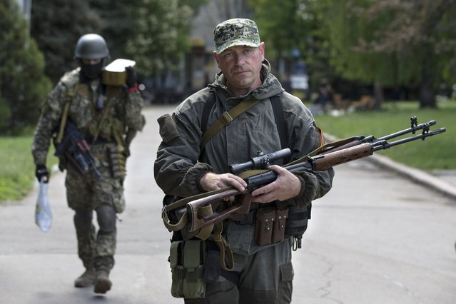 Pro-Russian gunmen carry their weapons at the local administration building in the center of Slovyansk, Ukraine, Tuesday, May 6, 2014. Gunbattles took place at various positions around the city Monday in what has proven the most ambitious government effort to date to quell unrest in the mainly Russian-speaking east. (Photo by Alexander Zemlianichenko/AP Photo)