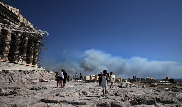 Tourists make their way next to the Parthenon temple as smoke from a raging wildfire rises in Athens, Greece July 17, 2015. (Photo by Alkis Konstantinidis/Reuters)