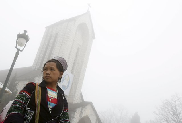 A handicraft vendor waits for customers on a foggy day in front of a Catholic church after Sunday Mass, in Vietnam's northern resort town of Sapa, north of Hanoi, February 21, 2016. (Photo by Reuters/Kham)