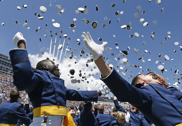 Air Force Academy graduates throw their caps into the air as F-16 jets from the Thunderbirds make a flyover, at the completion of the graduation ceremony for the class of 2014, at the U.S. Air Force Academy, in Colorado, on May 28, 2014. (AP Photo/Brennan Linsley)