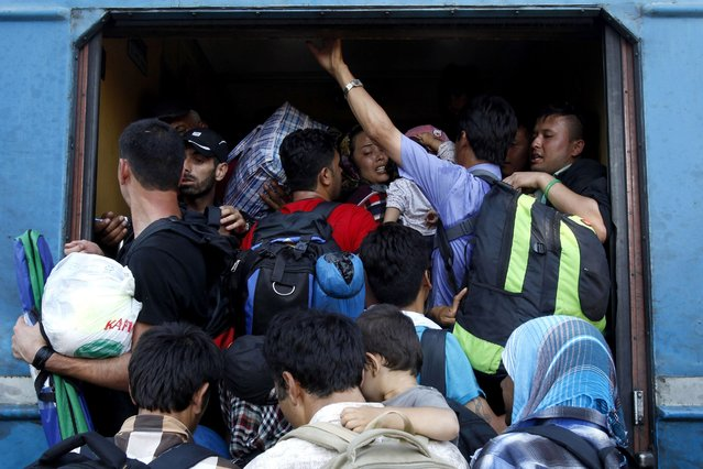 In this photo taken on Thursday, July 23, 2015 migrants  enter a train to Serbia at the railway station in the southern Macedonian town of Gevgelija. (Photo by Boris Grdanoski/AP Photo)