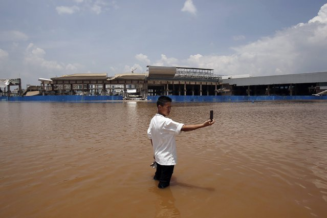 A resident takes a picture of himself standing in flood waters at a flooded area of Wujiaba airport in Kunming, Yunnan province June 10, 2014. Torrential rain will continue to sweep south and southwest China over the next three days, the National Meteorological Center said on Monday, Xinhua News Agency reported. (Photo by Reuters/Stringer)