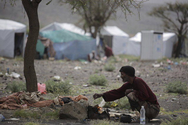 A displaced man cooks food outside his tent at a camp for internally displaced people in the outskirts of Sanaa, Yemen, Friday, May 27, 2016. Yemen's conflict pits the government, backed by the Saudi-led coalition, against Shiite rebels known as Houthis allied with a former president. Yemen's war has killed at least 6,200 civilians and injured tens of thousands of Yemenis, and 2.4 million people have been displaced, according to U.N. figures. (Photo by Hani Mohammed/AP Photo)