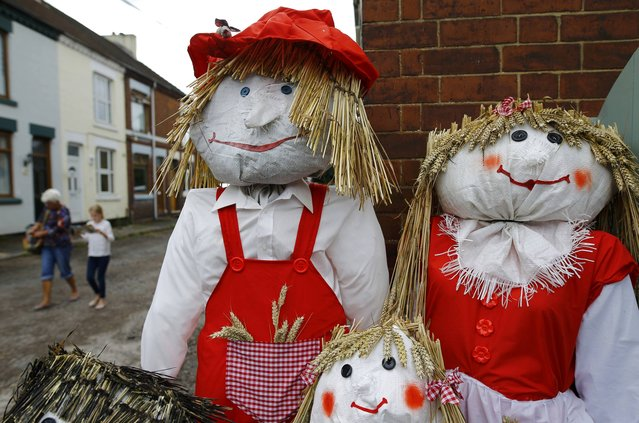 Visitors walk past a family of scarecrows during the Scarecrow Festival in Heather, Britain July 29, 2015. (Photo by Darren Staples/Reuters)