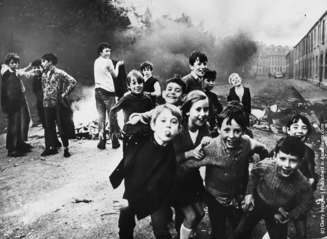 1971: Children jeer at British soldiers whiile a fire smoulders in the street behind them