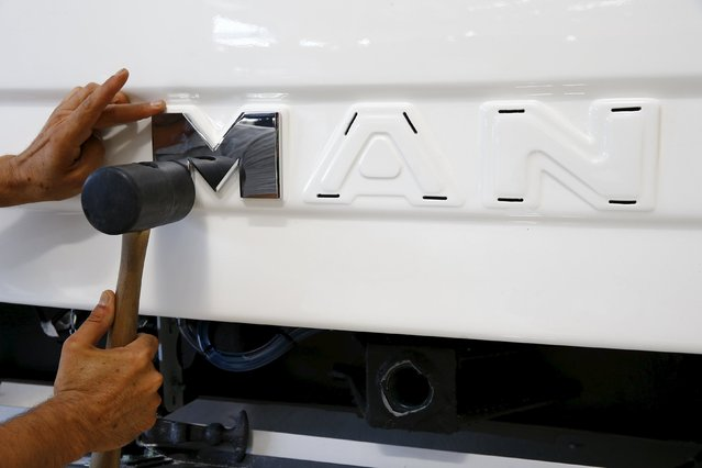 A worker hammers the logo of a bus at the assembly line of the MAN Bus Production Center in Ankara, Turkey, July 29, 2015. (Photo by Umit Bektas/Reuters)