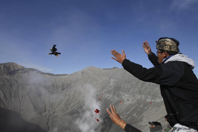 A worshipper throws chicken into the crater of Mount Bromo as an offering to the gods during Yadnya Kasada festival in Probolinggo, East Java, Indonesia, Saturday, August 1, 2015. (Photo by AP Photo/Trisnadi)