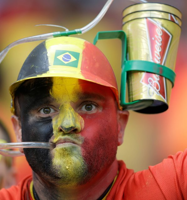 A Belgian fan drinks from his helmet cup before the group H World Cup soccer match between Belgium and Russia at the Maracana Stadium in Rio de Janeiro, Brazil, Sunday, June 22, 2014. (Photo by Natacha Pisarenko/AP Photo)