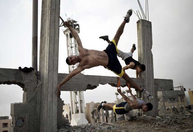 Palestinian group, Bar Palestine, take part in street exercises amid the destruction in Gaza City on August 3, 2015. Street workout, that is still new to Gaza, is a growing sport across the world with annual competitions and events. (Photo by Mohammed Abed/AFP Photo)