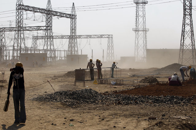 In this February 24, 2015 file photo, a worker covers his face to avoid rising dust at a coal-fired power plant, partially financed by the Japan Bank for International Cooperation, under construction in Kudgi, India. Led by cutbacks in China and India, construction of new coal-fired power plants is falling worldwide, improving chances climate goals can be met despite earlier pessimism, three environmental groups said Wednesday, March 22, 2017. (Photo by Aijaz Rahi/AP Photo)