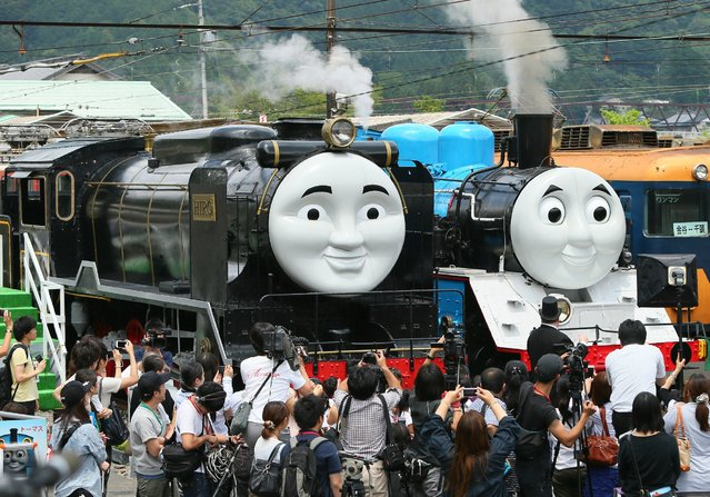 This picture taken on July 2, 2014 shows life-sized a Thomas the Tank Engine (R) and Hiro (L), surrounded by the media, at Senzu station on Japan's Oigawa railway, in the town of Kawanehon in Shizuoka prefecture, west of Tokyo. Rides on popular British character Thomas the Tank Engine will be offered to the public from July 12 through October 12 between Shinkanaya and Senzu stations. (Photo by AFP Photo/JIJI Press)