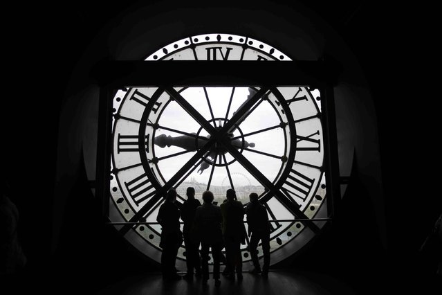 Visitors at the Musee d'Orsay are seen in silhouette as they look behind a giant clock face at the former Orsay railway station, in Paris, France July 28, 2015. The national museum of the Musee d'Orsay opened in December 1986 and it displays collections of art from the period 1848 to 1914.  France has been the world's most visited country since the 1980's, welcoming 84 million tourists last year. (Photo by Stephane Mahe/Reuters)