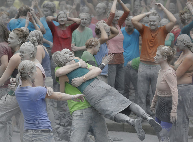 """Participants celebrate after the performance """"1000 Gestalten"""" with hundreds of people painted like clay figures moved slowly and silently through the streets of Hamburg to protest against the G-20 summit in Hamburg, northern Germany, Wednesday, July 5, 2017. (Photo by Matthias Schrader/AP Photo)"""