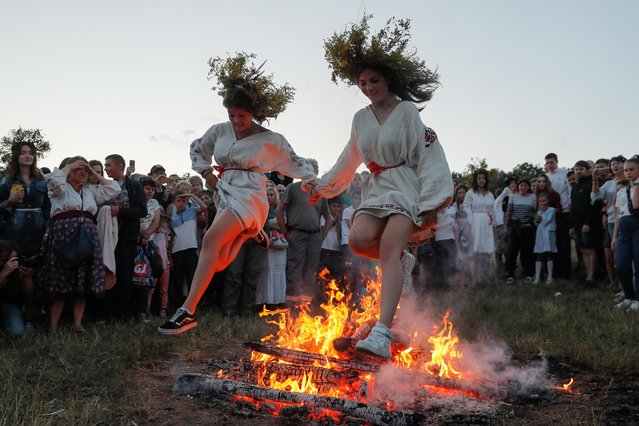 Ukrainians jump over a bonfire in Kiev, Ukraine, 06 July 2019, as they celebrate the traditional pagan holiday of Ivana Kupala. Ivana Kupala is celebrated, during the summer solstice, on the shortest night of the year, marking the beginning of summer and is celebrated in Ukraine, Belarus, Poland and Russia. People sing and dance around bonfires, play games and perform traditional rituals. Young people jump over bonfires in order to test their bravery. Couples holding hands jump over the flames to test their love. If the couple does not succeed it is predicted to split up. Traditionally, children and young unmarried women wear wreaths of wild flowers on their heads to symbolize purity. (Photo by Sergey Dolzhenko/EPA/EFE)