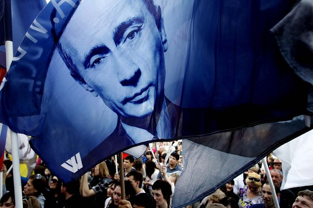 Pro-Putin activists hold flags with portraits of Russian president-elect Vladimir Putin during a rally on the eve of his inauguration as president in Moscow on May 6, 2012