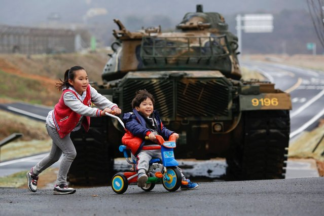 Children play in front of a tank on the island of Baengnyeong, which lies on the South Korean side of the Northern Limit Line (NLL), in the Yellow Sea April 12, 2014. (Photo by Damir Sagolj/Reuters)