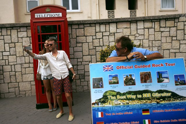 Tourists take a selfie next to a traditional red telephone box as they enter the British colony of Gibraltar at its border with Spain August 10, 2015. The British government on Sunday accused Spain of violating its sovereignty over Gibraltar, saying Spanish state vessels had repeatedly and unlawfully entered its territorial waters without notifying it. (Photo by Jon Nazca/Reuters)