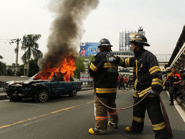 Filipino firemen extinguish a burning vehicle during an earthquake preparedness drill in Makati city, south of Manila, Philippines, 22 June 2016. Thousands of people participated in the Metro Manila earthquake drill to prepare residents of nearly 12 million for a feared magnitude-7.2 quake that could kill thousands and displace millions, Emerson Carlos head of the Metropolitan Manila Development Authority (MMDA) said. Philippines sits on the Pacific Ring of Fire, an area prone to seismic shifts that spark earthquakes and volcanic activity. (Photo by Francis R. Malasig/EPA)