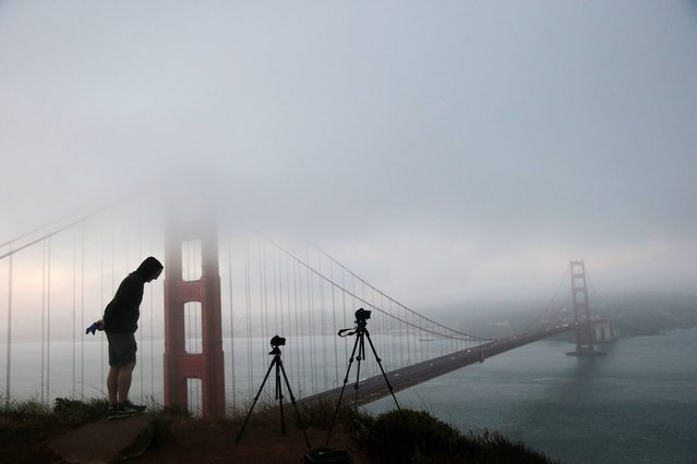 Russell Brown, of Los Altos, Calif., photographs the fog-covered Golden Gate Bridge from a a hill in the Marin Headlands on Monday, July 14, 2014, in San Francisco. (Photo by Marcio Jose Sanchez/AP Photo)