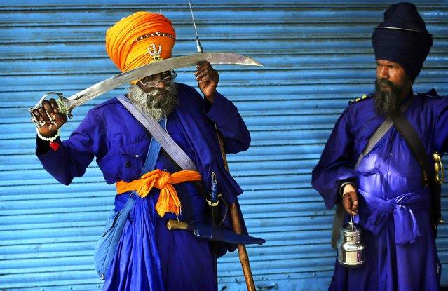 Indian Sikh Nihang holds his sword against his head to pray near the Sheesh Ganj Gurudwara Sikh temple in New Delhi, India on June 1, 2012