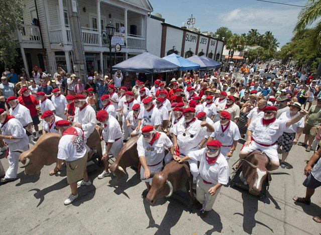 """Participants in the annual Ernest Hemingway look-alike contest kick off the """"Running of the Bulls"""" in Key West, Florida in this July 19, 2014 handout photo provided by the Florida Keys News Bureau. The event, a parody of its namesake in Pamplona, Spain, is one of many during Key West's Hemingway Days festival that continues through July 20, 2014. Hemingway lived and wrote in Key West throughout most of the 1930s. (Photo by Andy Newman/Reuters/Florida Keys News Bureau)"""