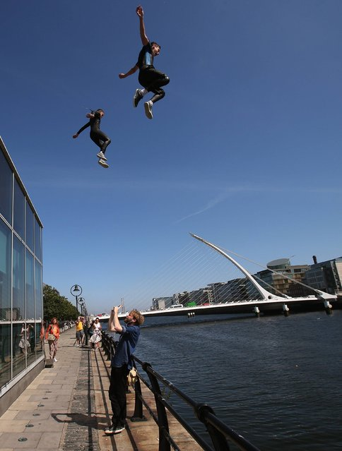 A passerby stops to video young people jumping into the River Liffey on North Wall Quay, Dublin, during the continuing good weather on July 25, 2014. (Photo by Brian Lawless/PA Wire)