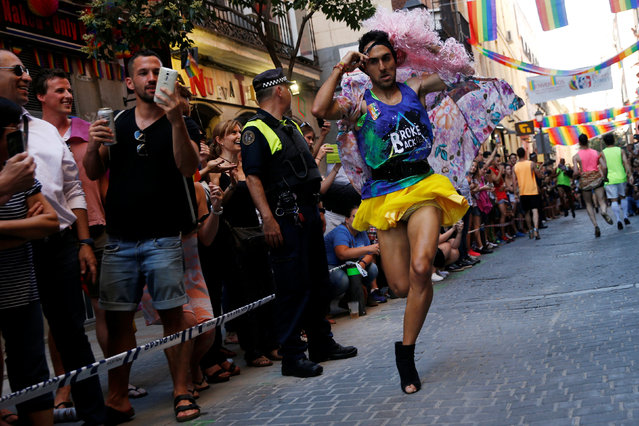 A competitor puts a dress and a wig on as he takes part in the annual race on high heels during Gay Pride celebrations in the quarter of Chueca in Madrid, Spain, June 30, 2016. (Photo by Susana Vera/Reuters)