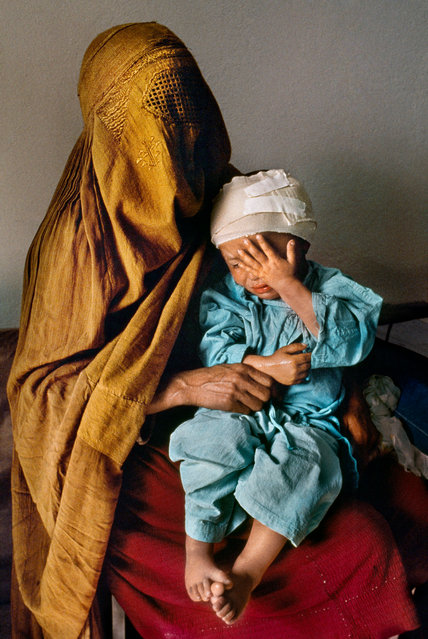 Kabul, 1992. A mother holds her two-year-old son, who was grazed by a stray bullet, at Karte Seh surgical hospital. (Photo by  Steve McCurry/Taschen/Magnum Photos/The Guardian)