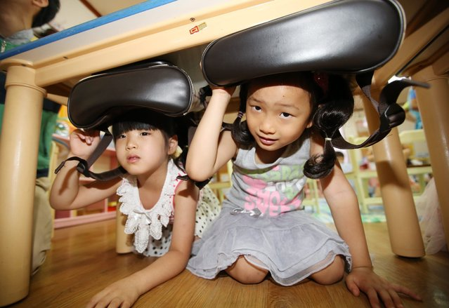 Preshoolers hide under their desks during an anti-quake drill at a preschool in Gwangju,some 339km south of Seoul, South Korea, 06 July 2016. The exercise came a day after a magnitude 5.0 earthquake occurred near the country's southeastern city of Ulsan with no fatalities or serious damage. (Photo by EPA/Yonhap)