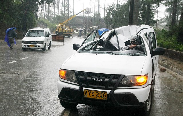 A resident drives a vehicle damaged by a fallen electric post after Typhoon Goni battered Baguio city in northern Philippines August 21, 2015. The Philippine Atmospheric, Geophysical and Astronomical Service Administration (PAGASA) state weather bureau reported on Friday that Typhoon Goni maintained its strength of maximum winds of 170 kilometers per hour (kph) near the center and gustiness of up to 205 kph. (Photo by Harley Palanchao/Reuters)
