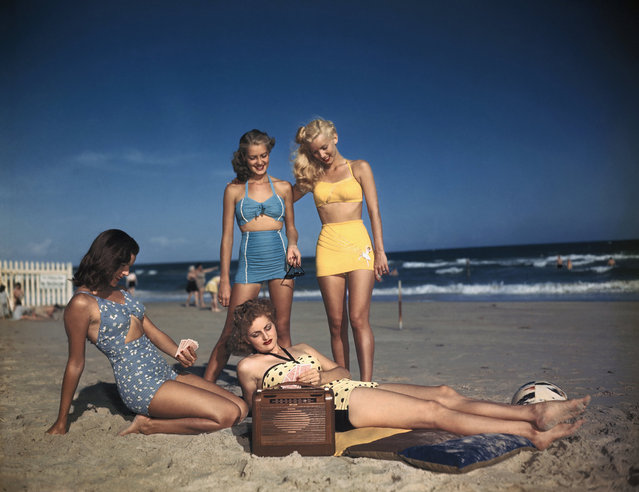 Bathing suit models are shown listening to the radio on the beach, circa 1940's. (Photo by Bettmann Archive/Getty Images)