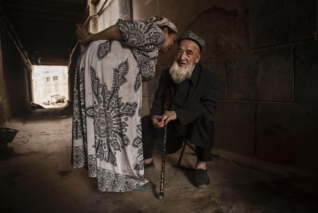 An elderly Uyghur man who said he was 100 years old listens to his wife as they sit in an alleyway before breaking their fast before the Eid holiday  on July 28, 2014 in old Kashgar, Xinjiang Province, China. (Photo by Kevin Frayer/Getty Images)