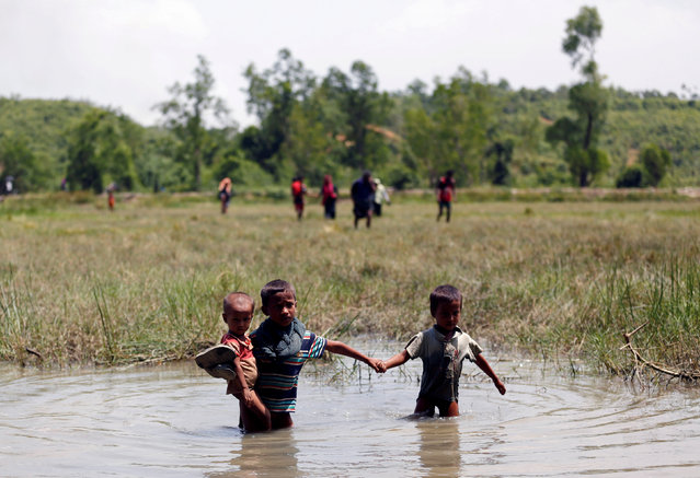 Rohingya children make their way through water as they try to come to the Bangladesh side from No Man's Land after a gunshot being heard on the Myanmar side, in Cox's Bazar, Bangladesh August 28, 2017. (Photo by Mohammad Ponir Hossain/Reuters)