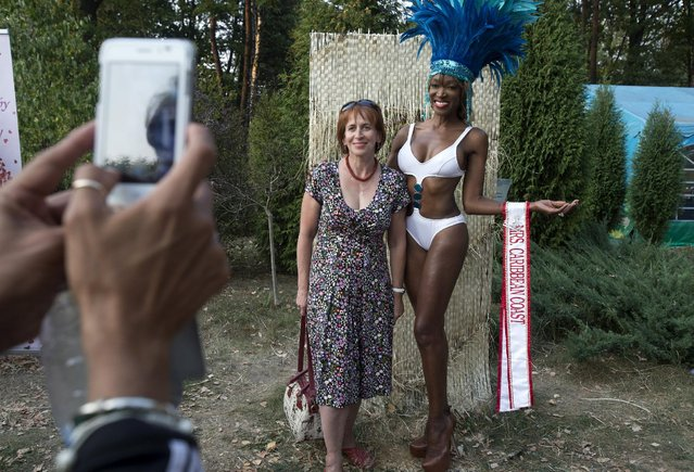 "A participant of the ""Mrs Universe 2015"" contest from Caribbean Coast, Mayra Joli poses for a photo with a woman during their visit in central botanical garden in Minsk, Belarus, August 25, 2015. (Photo by Vasily Fedosenko/Reuters)"