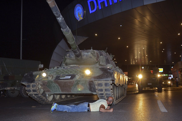 A man lays in front of a tank in the entrance to Istanbul's Ataturk airport, early Saturday, July 16, 2016. Members of Turkey's armed forces said they had taken control of the country, but Turkish officials said the coup attempt had been repelled early Saturday morning in a night of violence, according to state-run media. (Photo by Ismail Coskun/IHA via AP Photo)