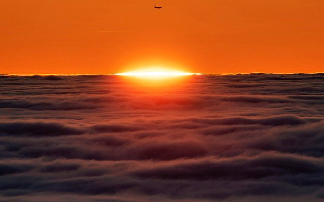 A plane passes the sun that rises over the morning fog above Frankfurt, Germany, Friday, January 24, 2020. (Photo by Michael Probst/AP Photo)