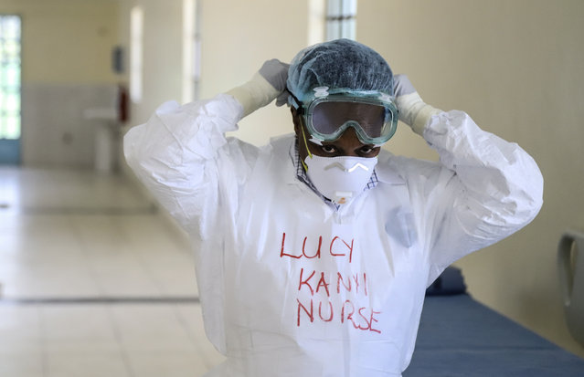 In this Friday, March 6, 2020 file photo, Kenyan nurse Lucy Kanyi, with her name written on her protective clothing so she can be recognized when wearing it, demonstrates to media the facilities and protective equipment to be used to isolate and treat coronavirus cases, at the infectious disease unit of Kenyatta National Hospital in the capital Nairobi, Kenya. Authorities in Kenya said Friday, March 13, 2020, that a Kenyan woman who recently traveled from the United States via London has tested positive for the new COVID-19 coronavirus, the first case in the East African country. For most people, the new coronavirus causes only mild or moderate symptoms, such as fever and cough. For some, especially older adults and people with existing health problems, it can cause more severe illness, including pneumonia. (Photo by Patrick Ngugi/AP Photo/File)