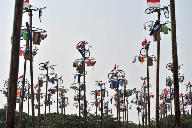 "Flags and various prizes, including bicycles, sit at the top of poles before that start of a local competition called ""panjat pinang"" in which people try to climb greased poles to get the prizes, during an event to celebrate Indonesia's Independence Day in Jakarta on August 17, 2014. (Photo by Adek Berry/AFP Photo)"