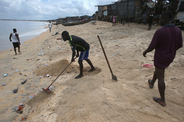 A boy rakes feces into a hole on the beach in the West Point slum on August 19, 2014 in Monrovia, Liberia. With a population of 75,000 people in a small area with poor sanitation, sickness is common in the township. A holding center in West Point for people suspected of having the Ebola virus was overrun and shut down by a crowd on August 16. (Photo by John Moore/Getty Images)
