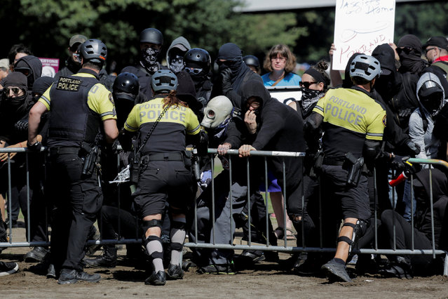 Police officers hold up a barricade against a crowd of black-clad demonstrators counter protesting against right-wing group Patriot Prayer in Portland, Oregon, U.S. September 10, 2017. Patriot Prayer announced they were moving their Sunday rally from downtown Portland to nearby Vancouver, Washington, citing fears for their safety. (Photo by Elijah Nouvelage/Reuters)