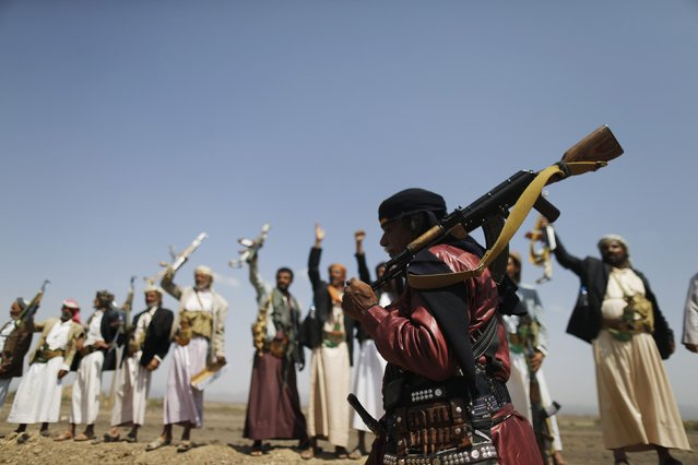 A follower of the Shi'ite Muslim Houthi group carries his weapon on his shoulder as he attends an anti-government gathering in Arhab, north of Yemen's capital Sanaa August 17, 2014. The Houthis, who control much of the northern Saada province bordering Saudi Arabia, are trying to consolidate their power in the north as the country moves towards a federal system that gives more power to regional authorities. (Photo by Khaled Abdullah/Reuters)
