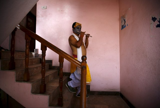 A reveller depicting Lord Krishna, a Hindu deity, walks down stairs to take part in a LGBT (lesbian, gay, bisexual and transgender) pride parade to mark Gaijatra Festival, also known as the festival of cows, in Kathmandu, Nepal, August 30, 2015. (Photo by Navesh Chitrakar/Reuters)