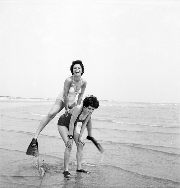 Two women wearing fins play leap-frog on the beach, 1955. (Photo by Peter Purdy)