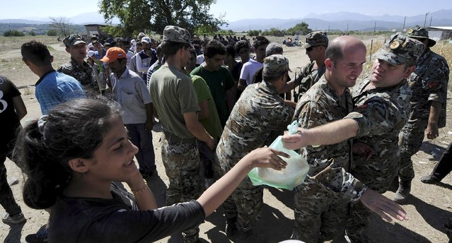 Macedonian soldiers distribute food to migrants in Macedonia near Gevgelija at the border with Greece September 1, 2015. (Photo by Ognen Teofilovski/Reuters)