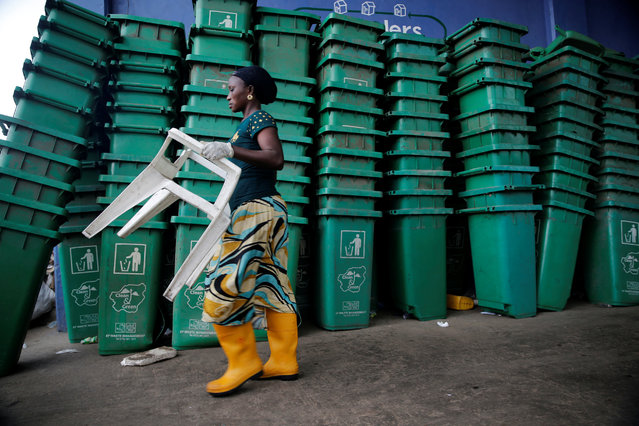A woman carries a plastic chair as she walks past a pile of litter bins at Wecycler recycling  centre in Ebutte Meta district in Lagos, Nigeria July 28, 2016. (Photo by Akintunde Akinleye/Reuters)