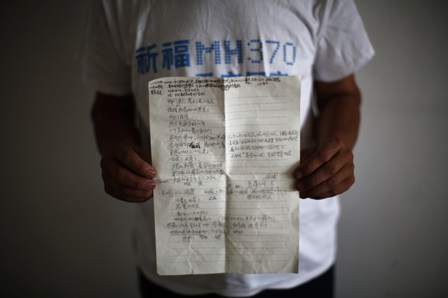 Zhang Yongli, whose daughter Zhang Qi was onboard Malaysia Airlines Flight MH370 which disappeared on March 8, 2014 shows a note featuring a poem which Zhang wrote for his daughter, during an interview with Reuters in Beijing July 22, 2014. (Photo by Kim Kyung-Hoon/Reuters)