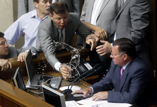 A deputy, Oleg Lyashko (L), douses vice-speaker of the Ukrainian parliament, Adam Martynyuk, with tea during an extraordinary session of the Ukrainian parliament in Kiev July 30, 2012. (Photo by Reuters/Stringer)